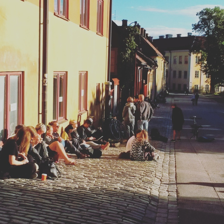 Locals sitting in the sun in Nytorget square in Södermalm